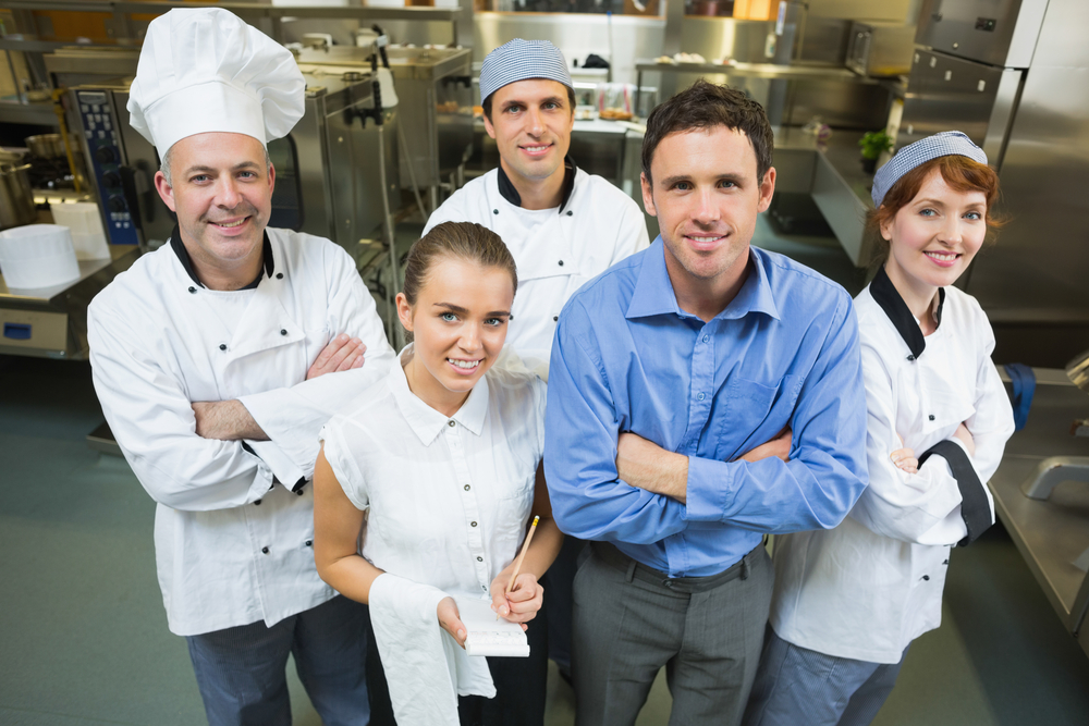 Handsome manager posing with some chefs and waitress in a kitchen